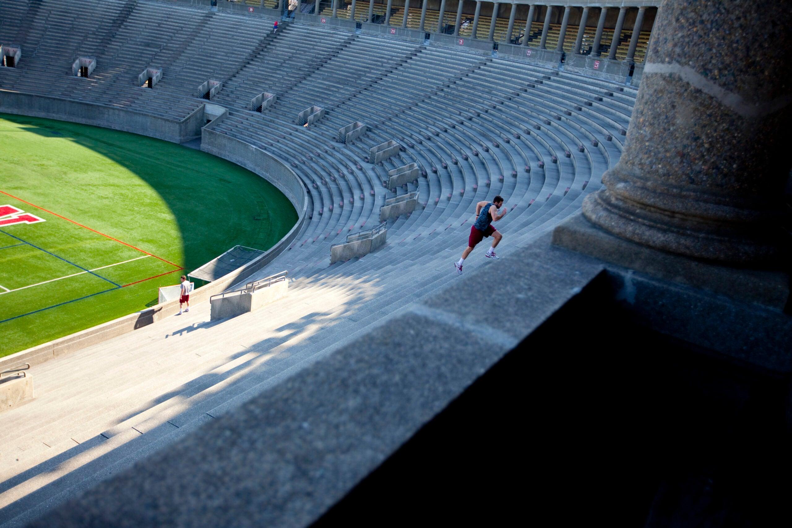 A man running up the steps in Harvard stadium