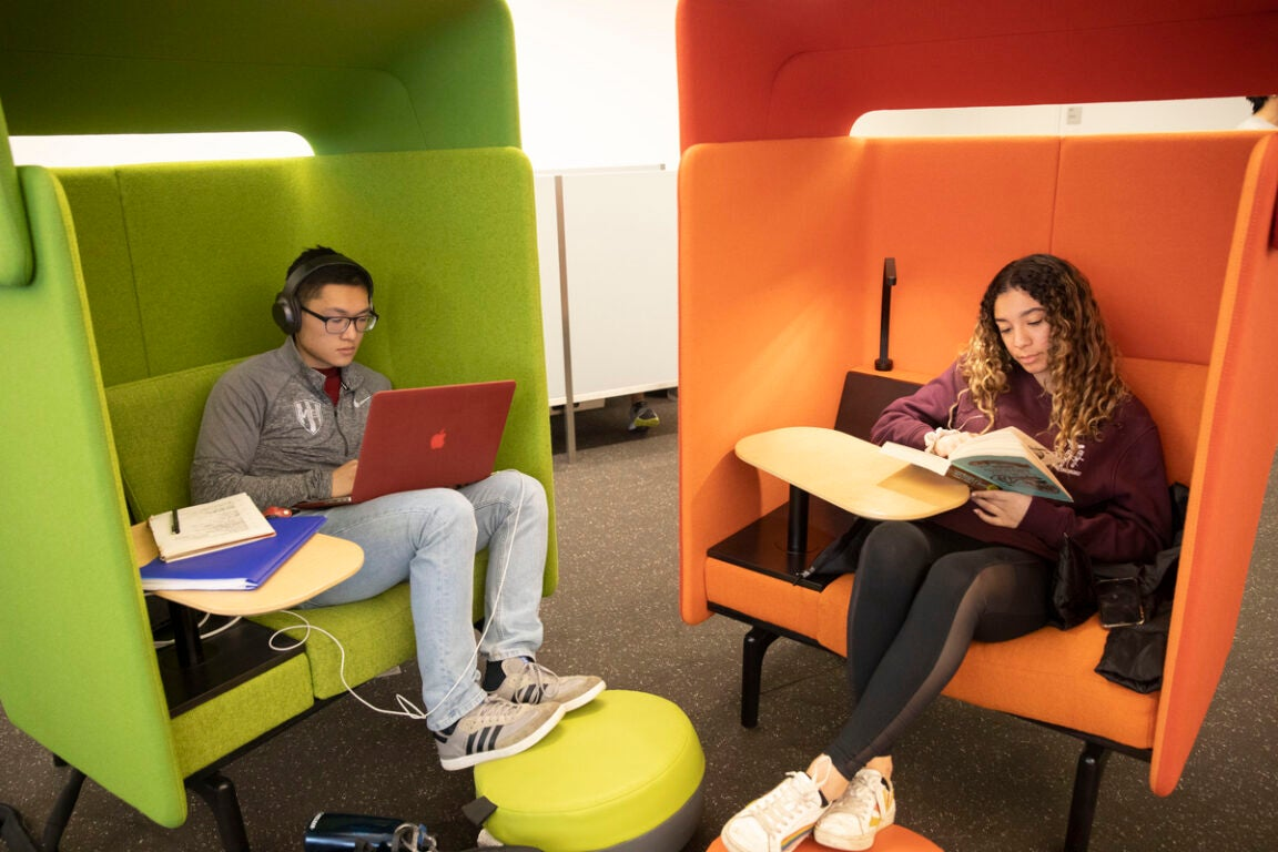 Two students study in green and orange chairs.