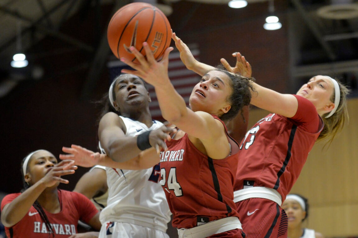Three women reaching for a basketball.