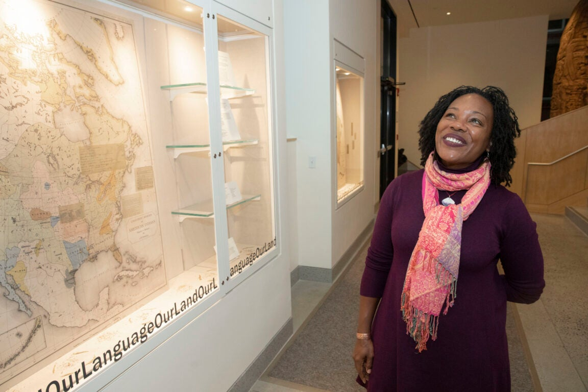 A woman stands by an art exhibit smiling.