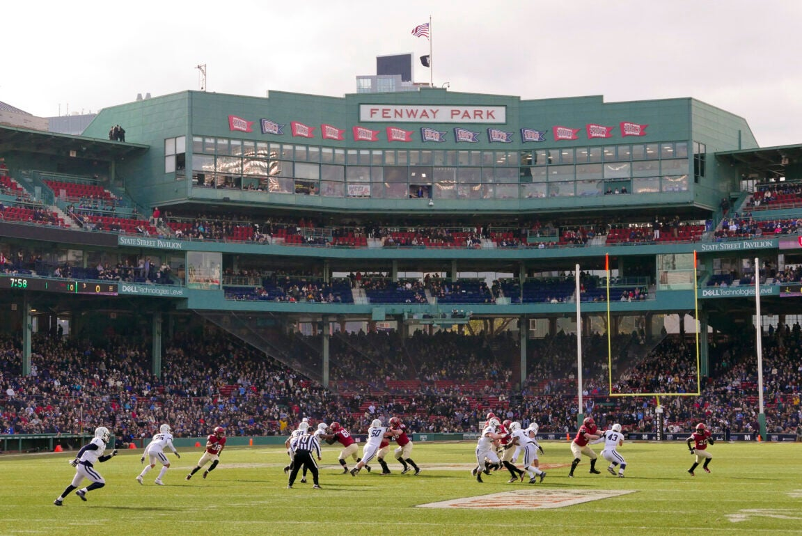 Harvard and Yale football teams playing in front of the large, green Fenway Park sign in the stadium.