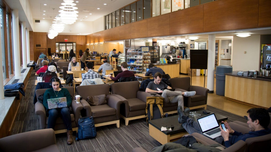 A room filled with students sitting on couches studying.