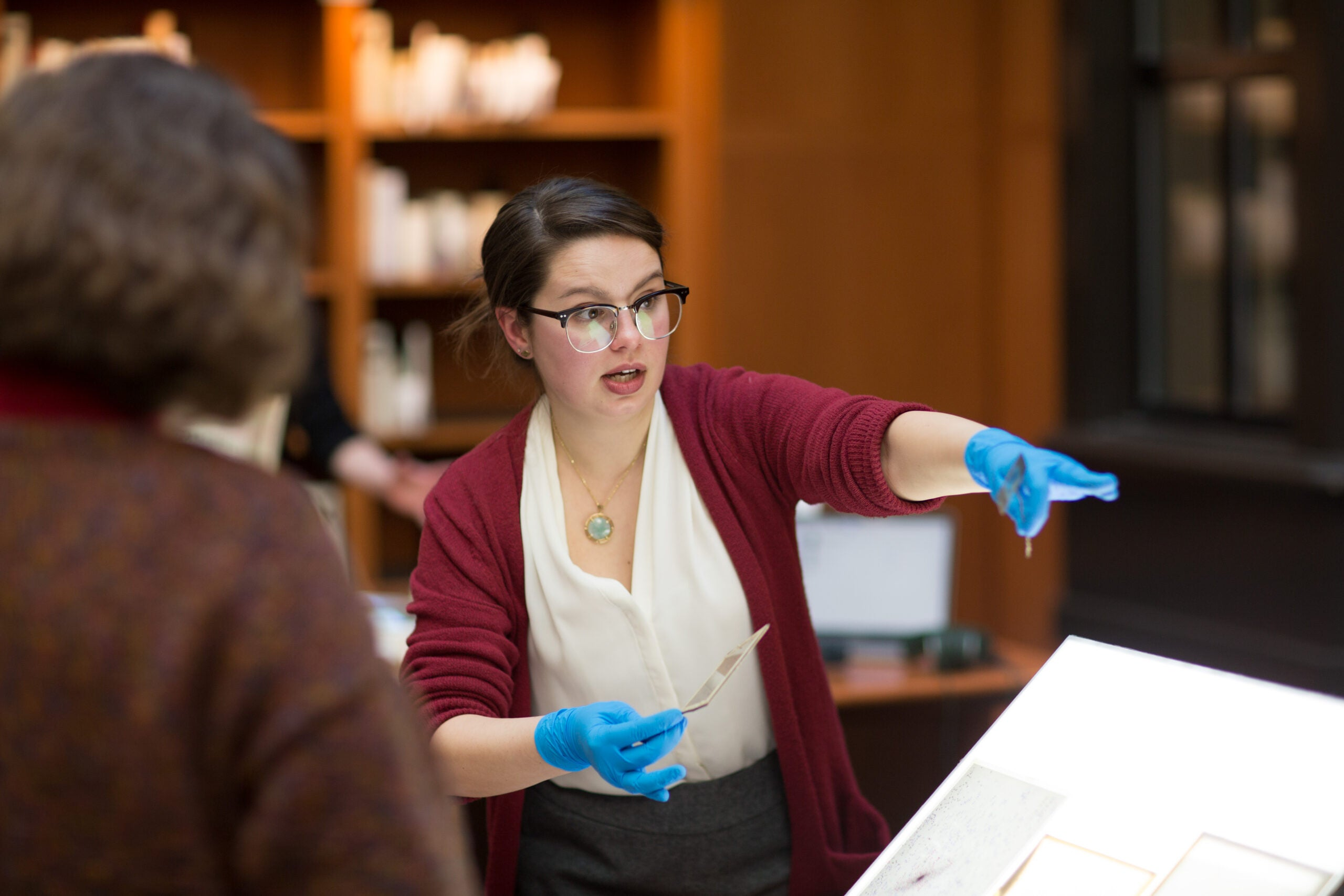 A librarian wearing gloves shows an exhibition in the library.