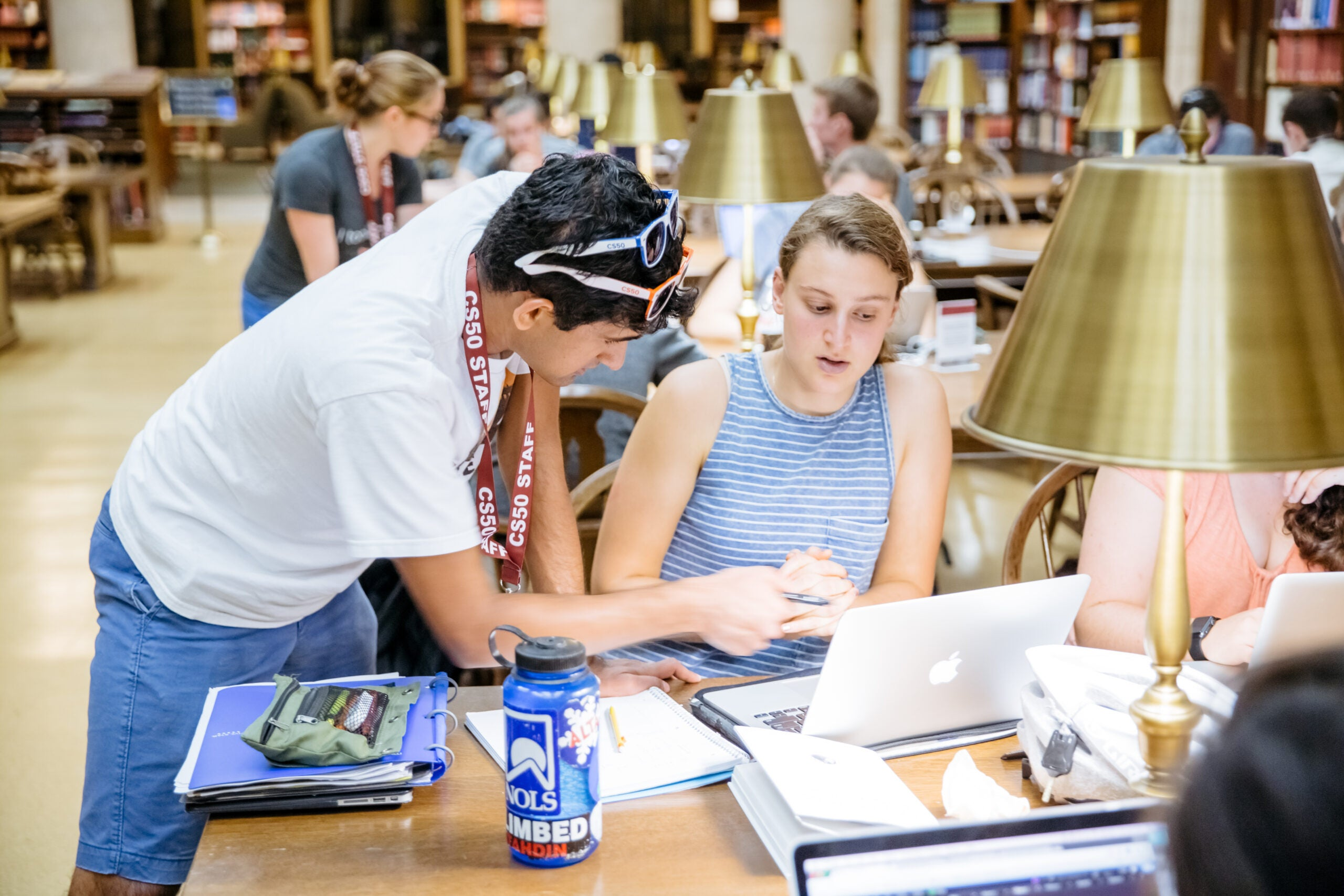 A student leans over another student looking at her laptop at the library.