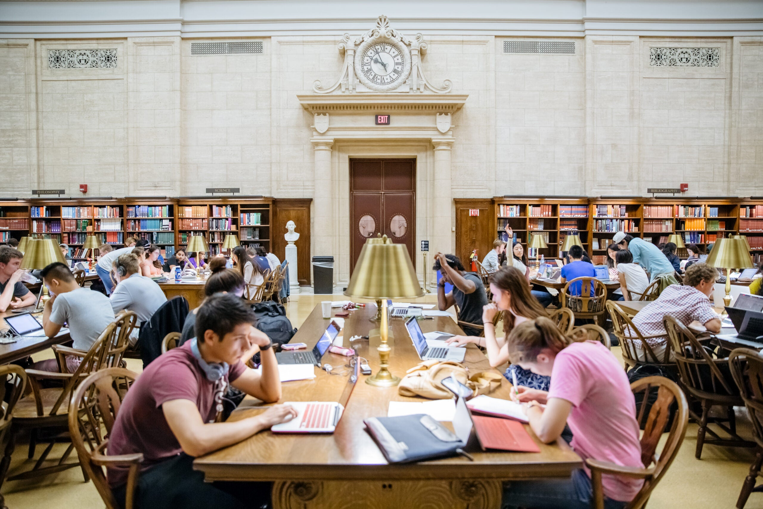 Library desks filled with students.