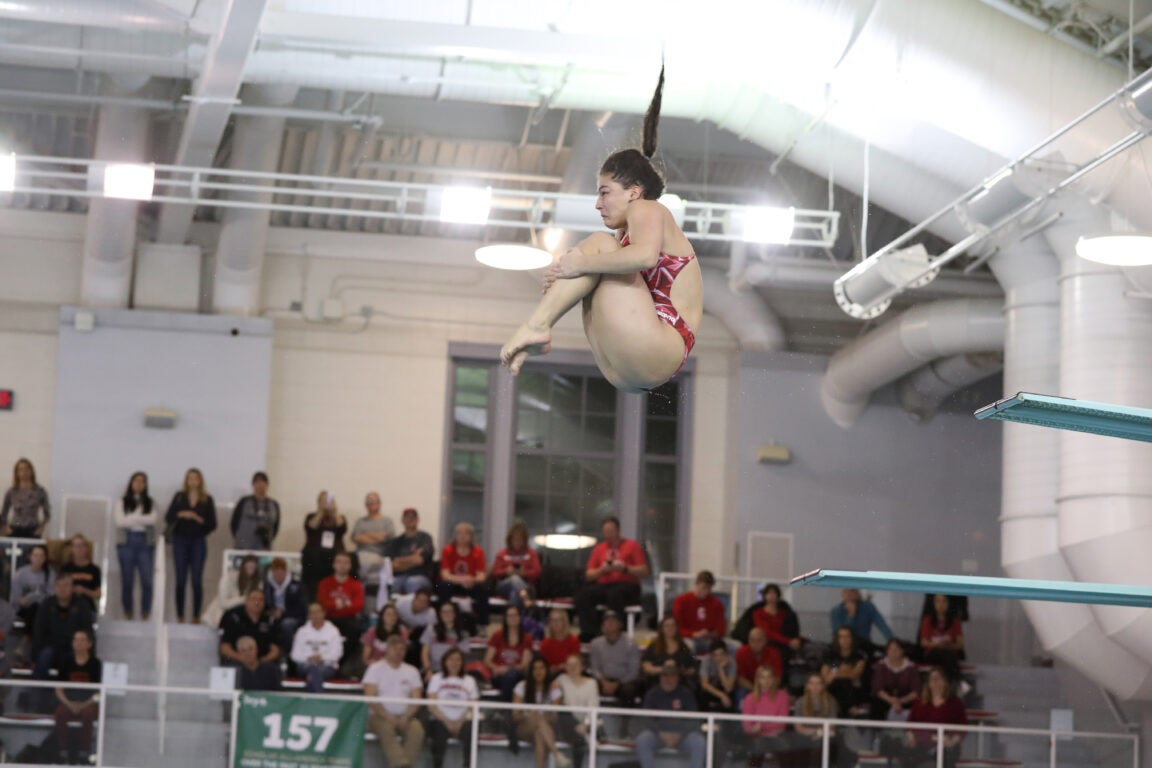 A woman mid-spin in a diving routine.