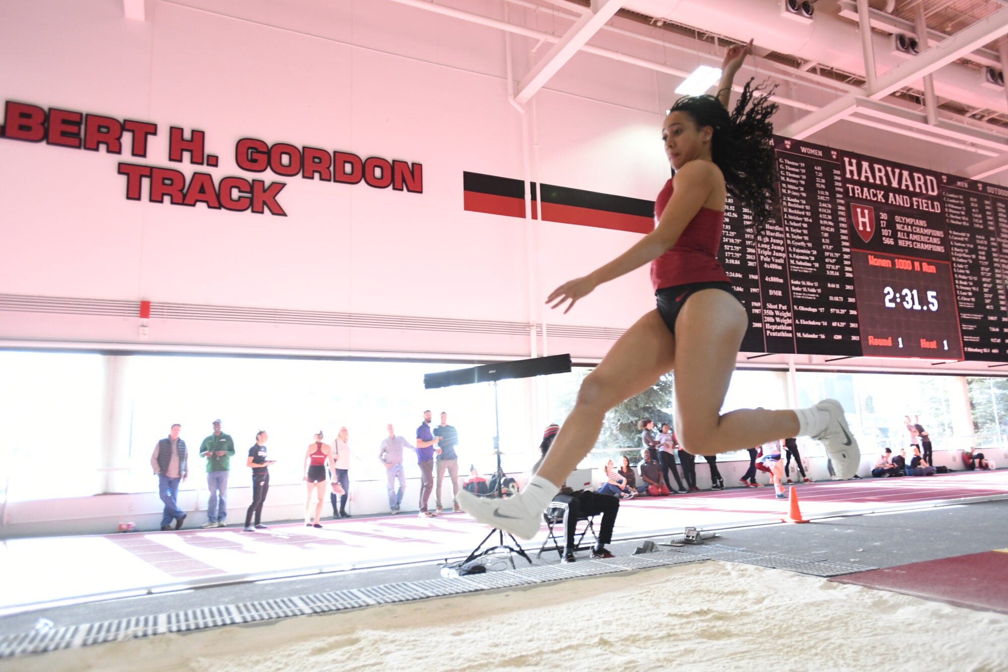 A woman leaping into a sand pit.