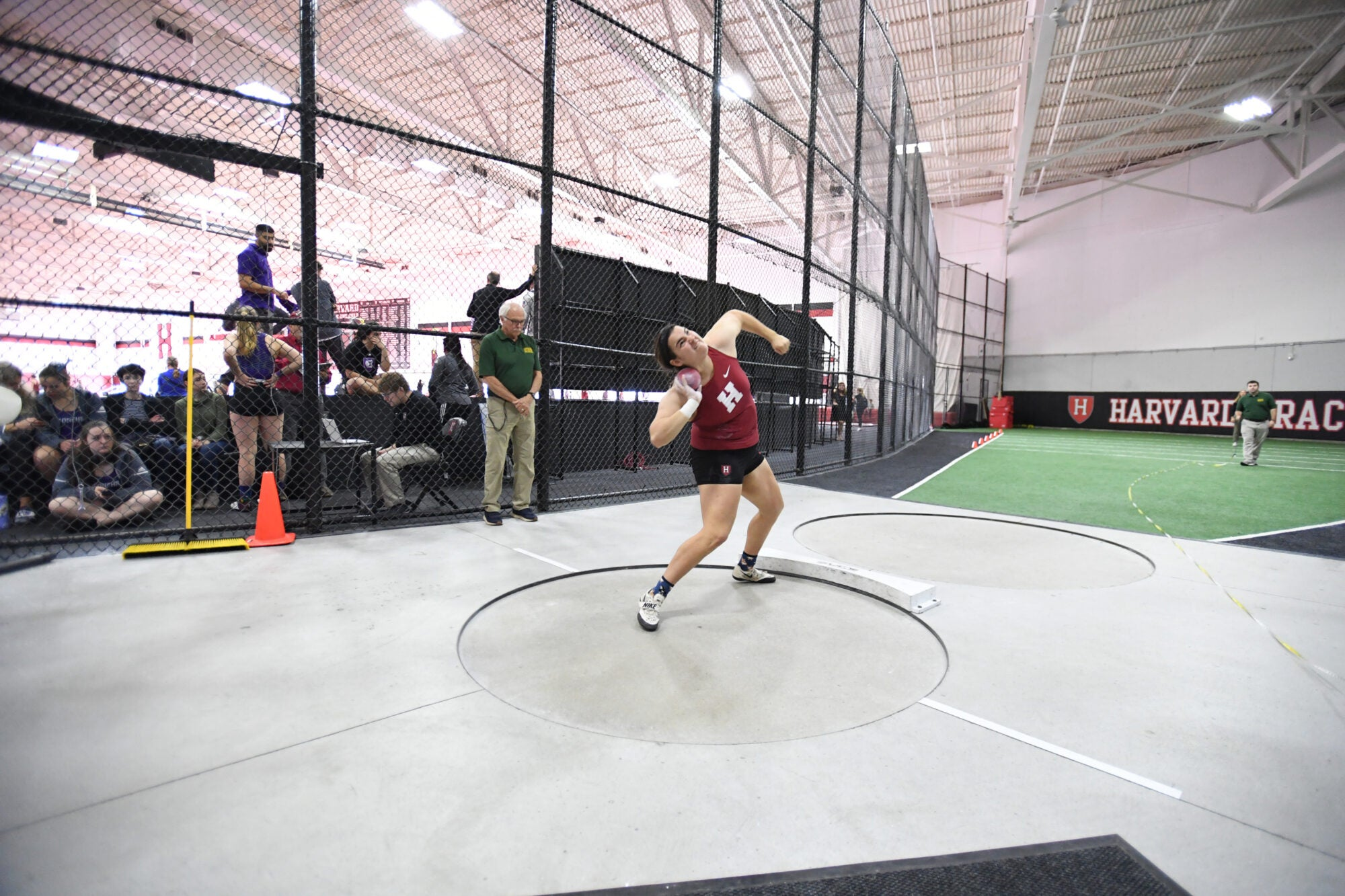 A woman with a small ball on her shoulder ready to throw.