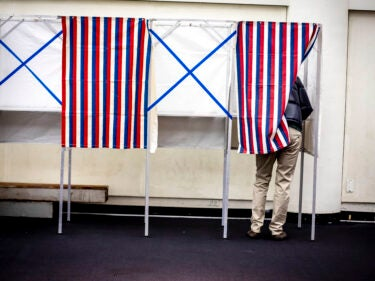 Some standing in a voting booth
