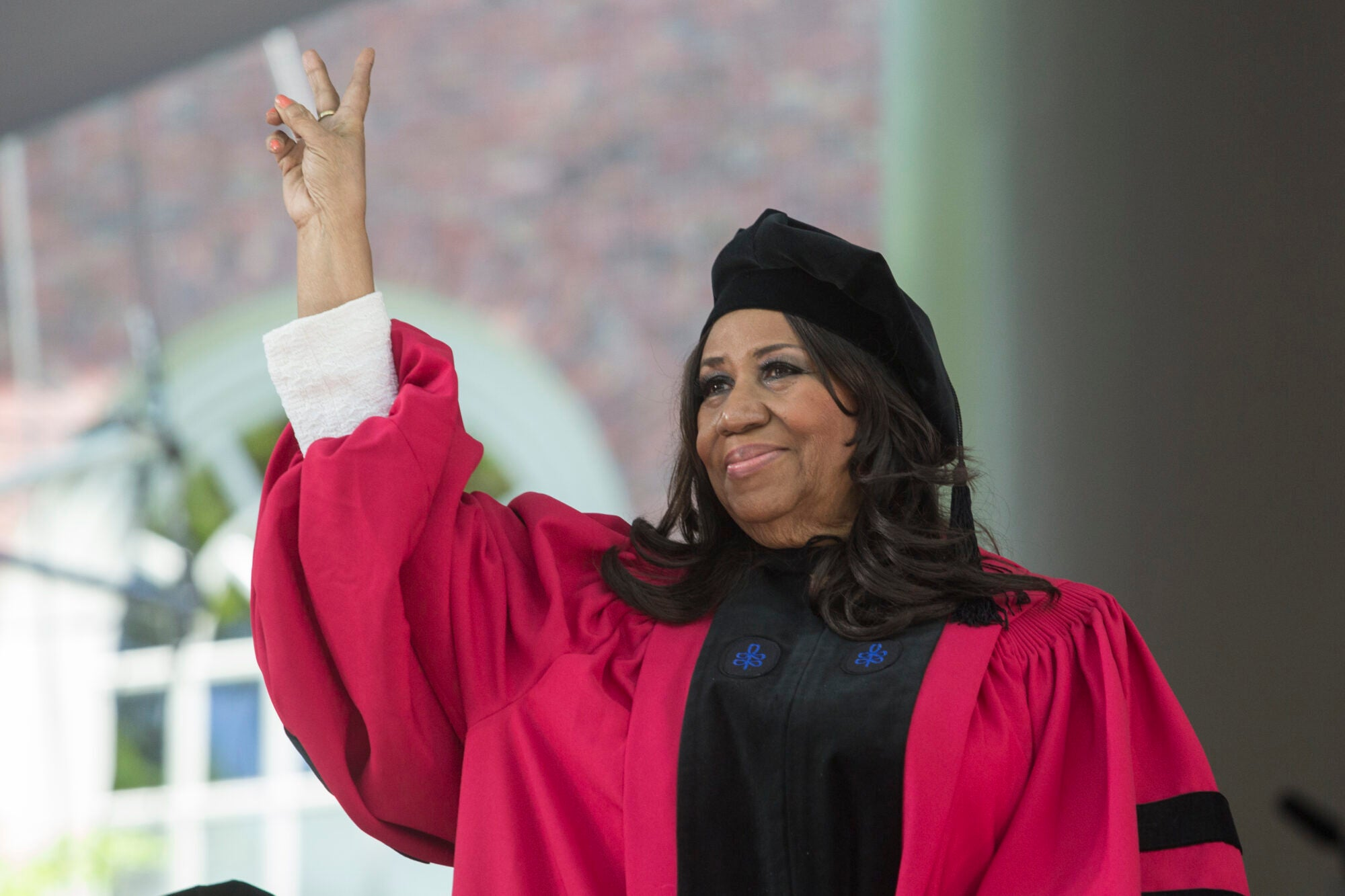 Aretha Franklin waving to the audience in her cap and gown.