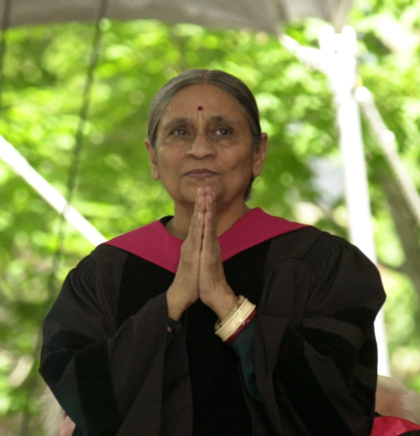 An Indian woman with her hands clasped in front of her mouth