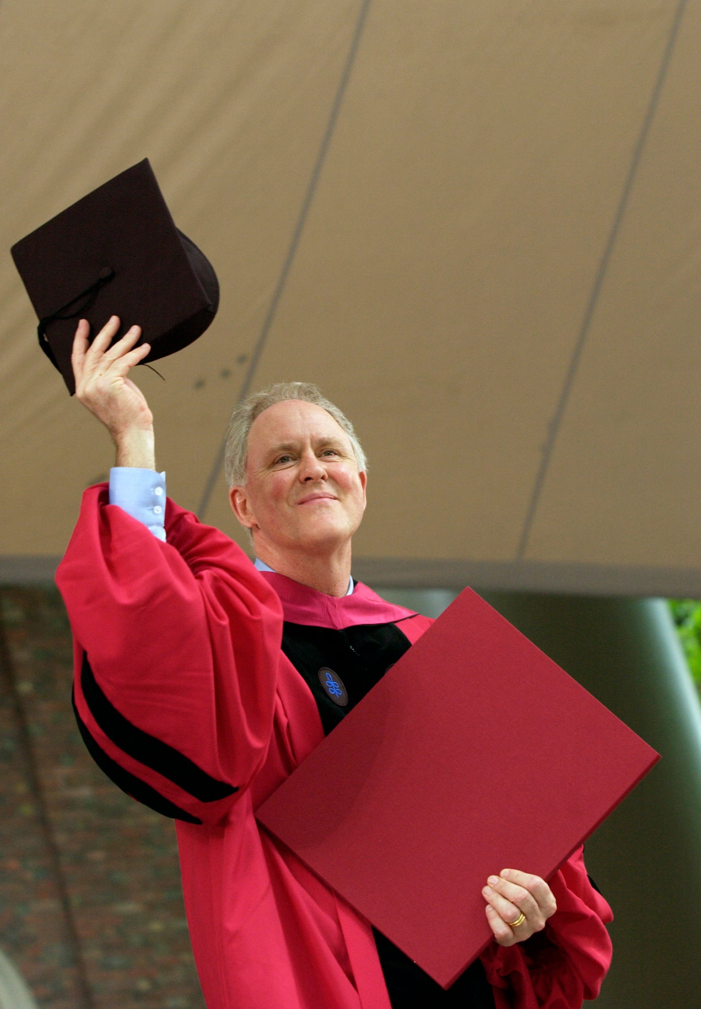 John Lithgow holding up his cap while wearing a gown
