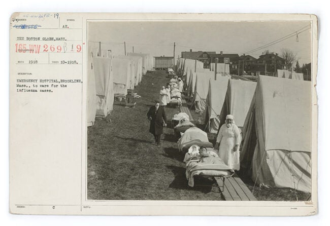 Image from 1918 of flu tents set up with patients in beds set up in front of them.