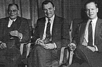 three men in suits seated.
