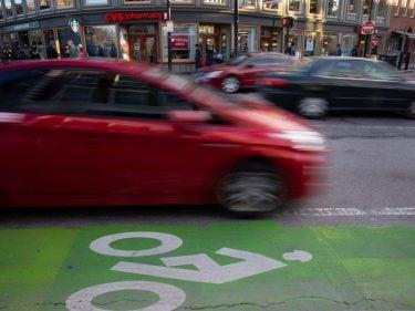 A car driving next to a bike lane