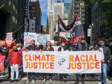 A group of protesters with a sign that says climate justice is racial justice