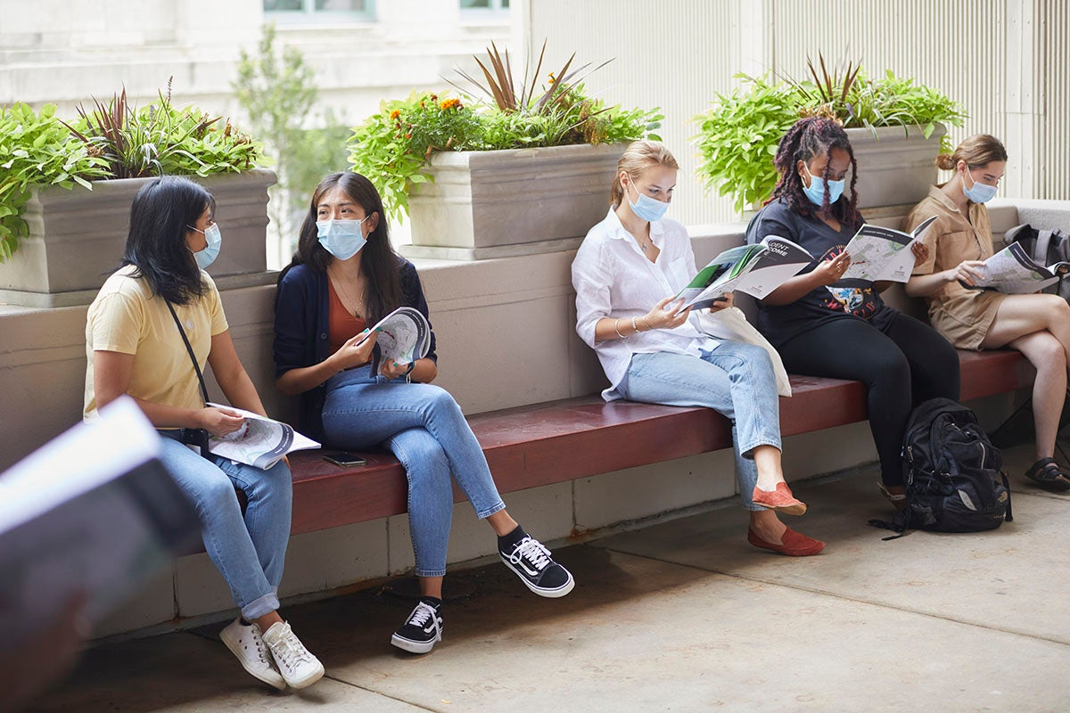 Five students wearing masks sit on a bench