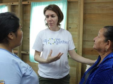 Woman in a white shirt talking with two women