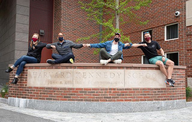 """Four students sit far apart on a wall that reads """"Harvard Kennedy School"""""""