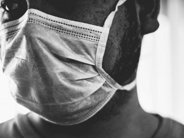 A black and white photo of a man wearing a face covering