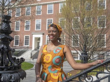 A student wearing a brightly colored dress stands on the Harvard campus