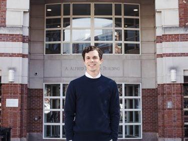 Jeremy Ney in a sweater outside a building