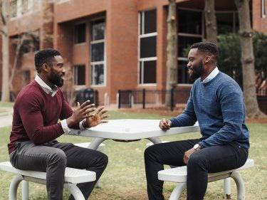 Jamaji and Onyema Nwanaji-Enwerem talking at a picnic table