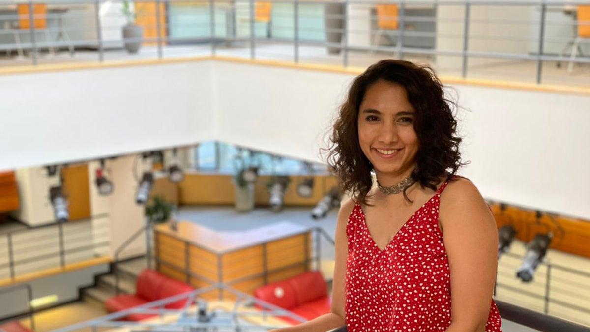 Monica Pesswani standing on a balcony inside a building