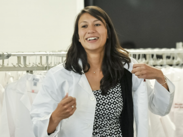 A woman puts on her new medical white coat