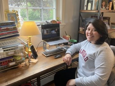 A student sits at a desk with a laptop