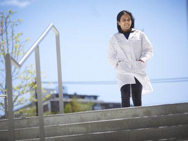 Sneha Dutta outside in a white lab coat