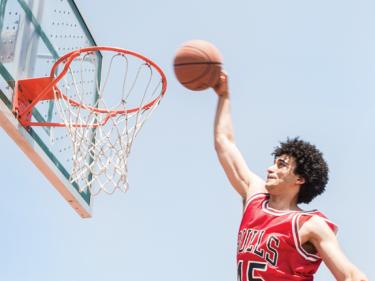 A man in a bulls jersey dunking a basketball
