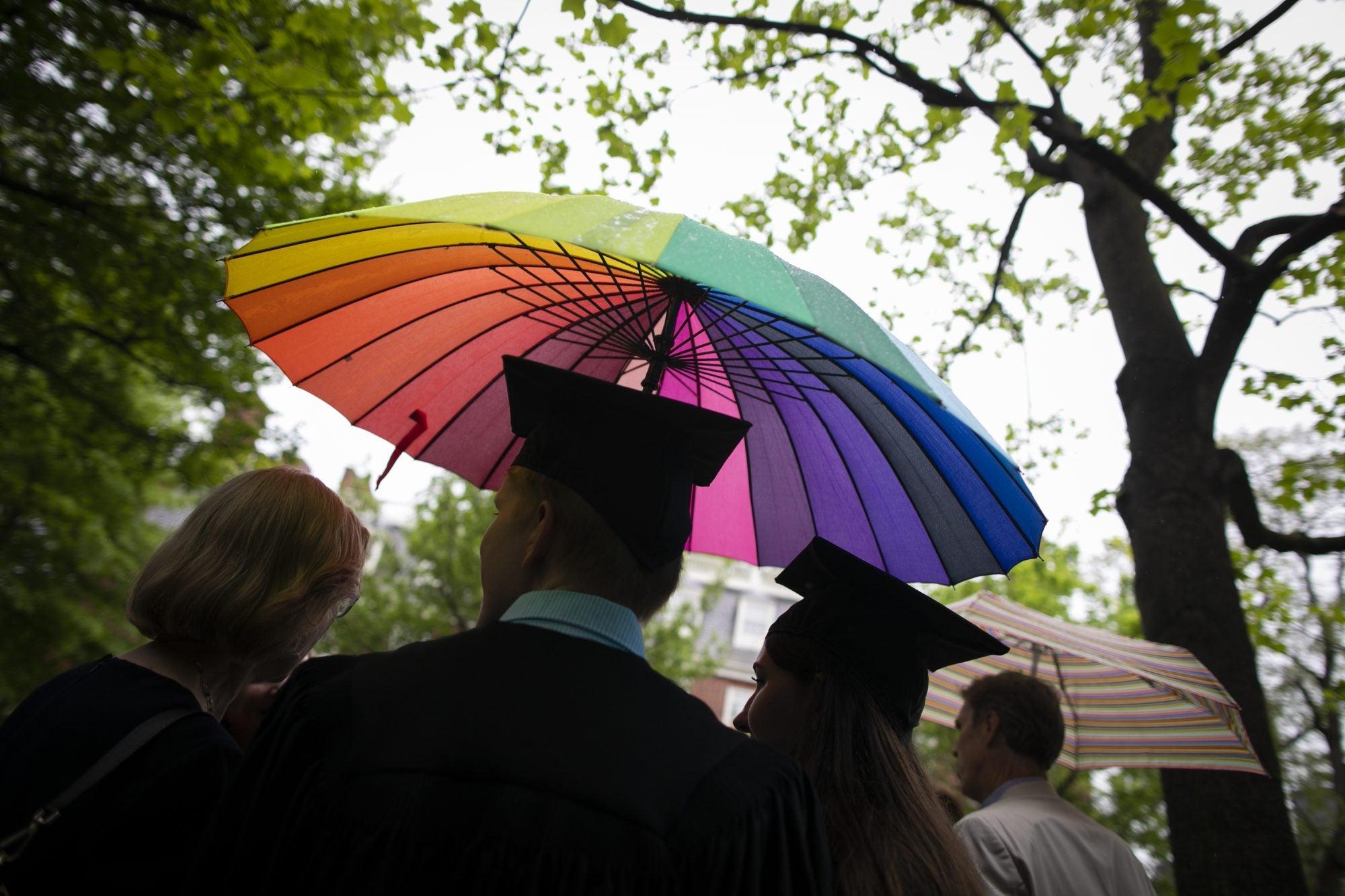 A rainbow umbrella overhead of graduates