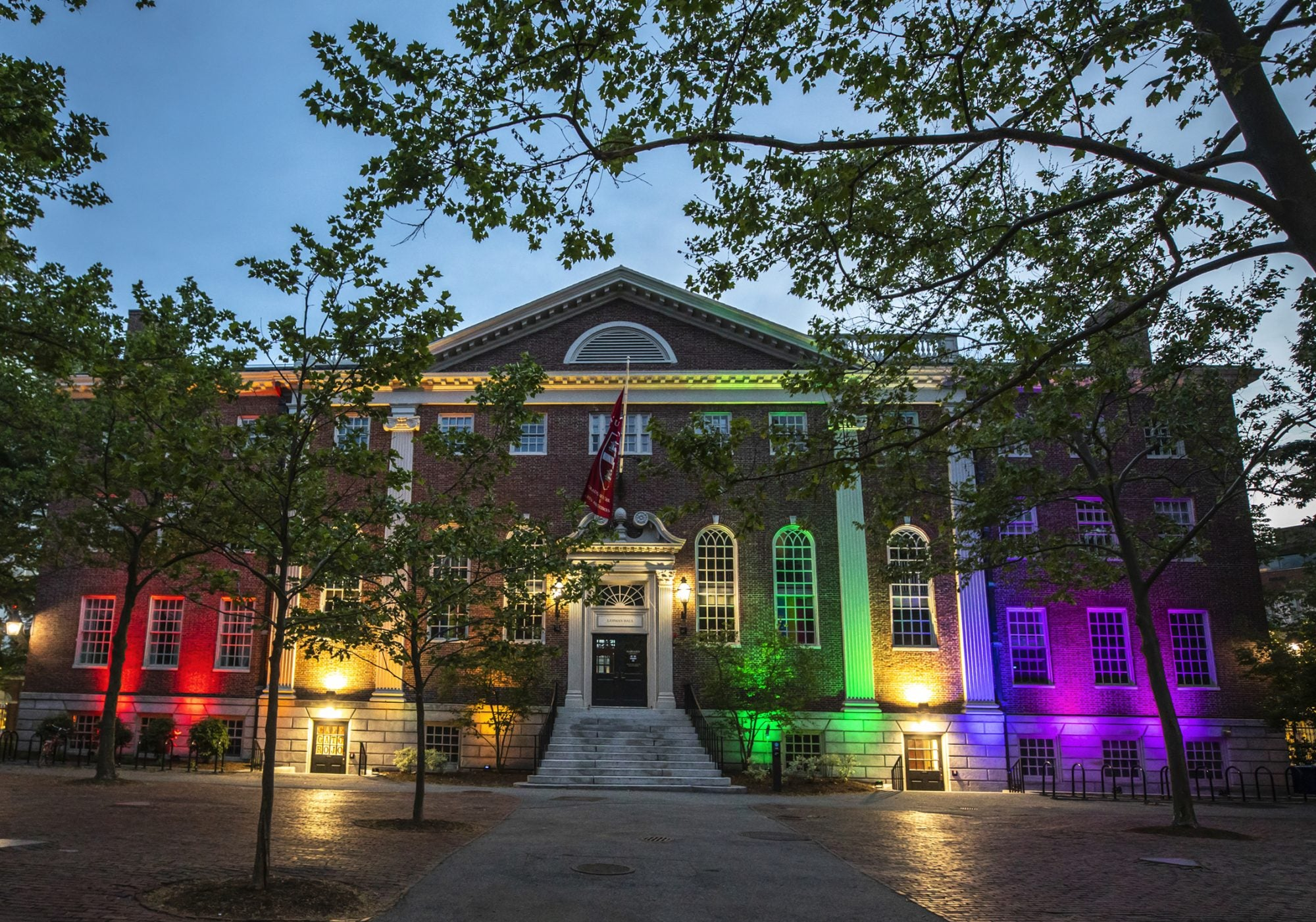 A brick building with rainbow lights in front