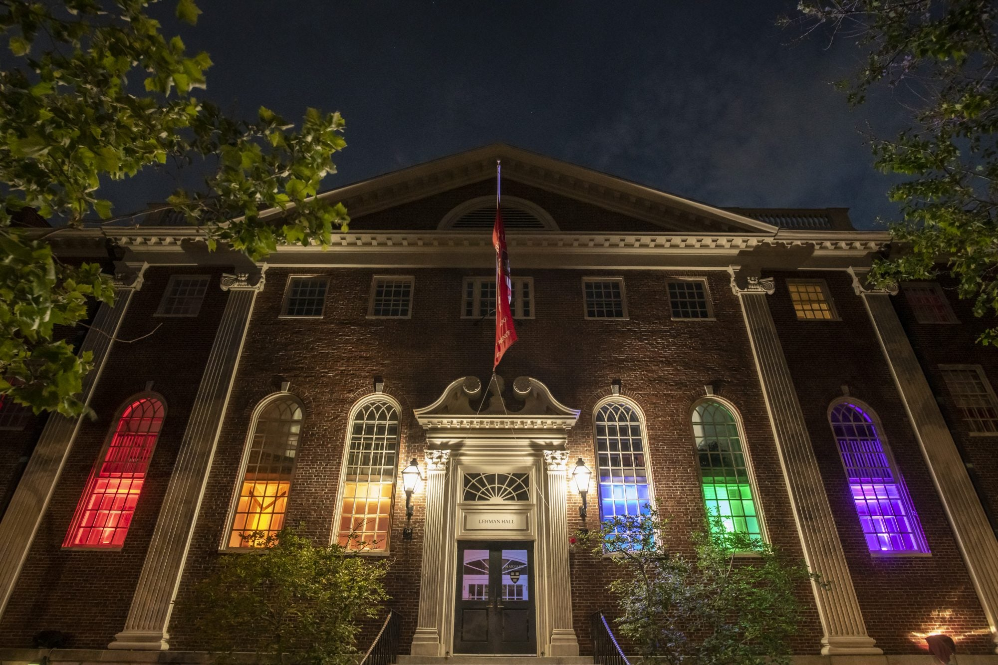Rainbow lights in the windows of a brick building