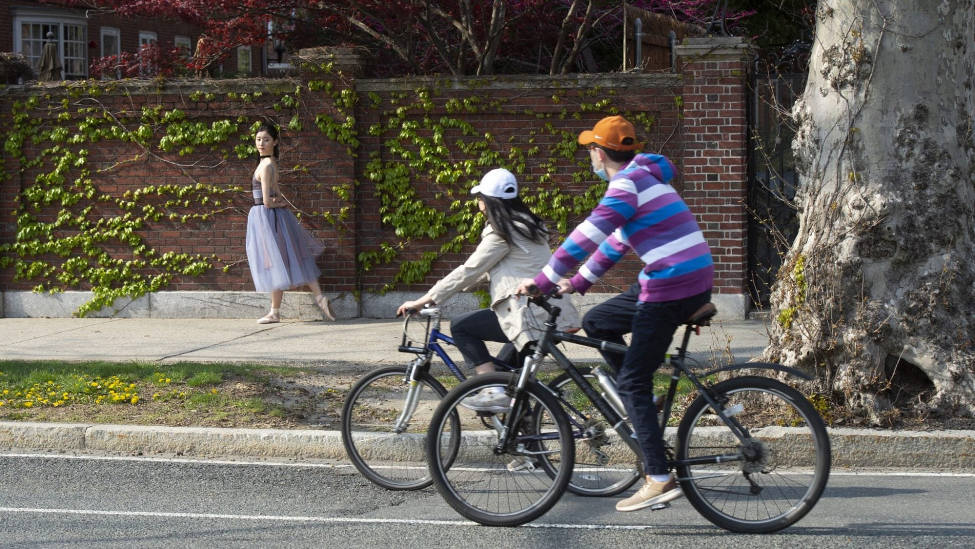 Two people biking while a woman does ballet