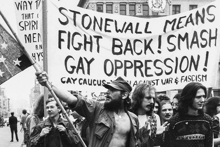 """A black and white photo of protesters with a sign that reads, """"Stonewall means fight back! Smash gay oppression!"""""""