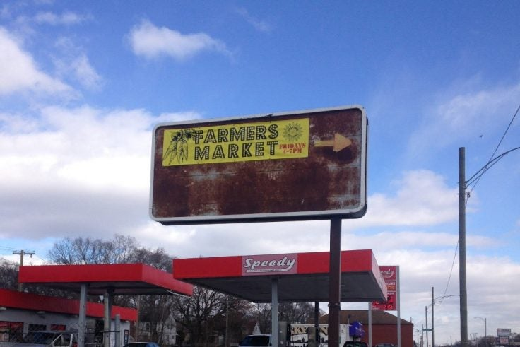 A rusty store sign advertising a farmers market.