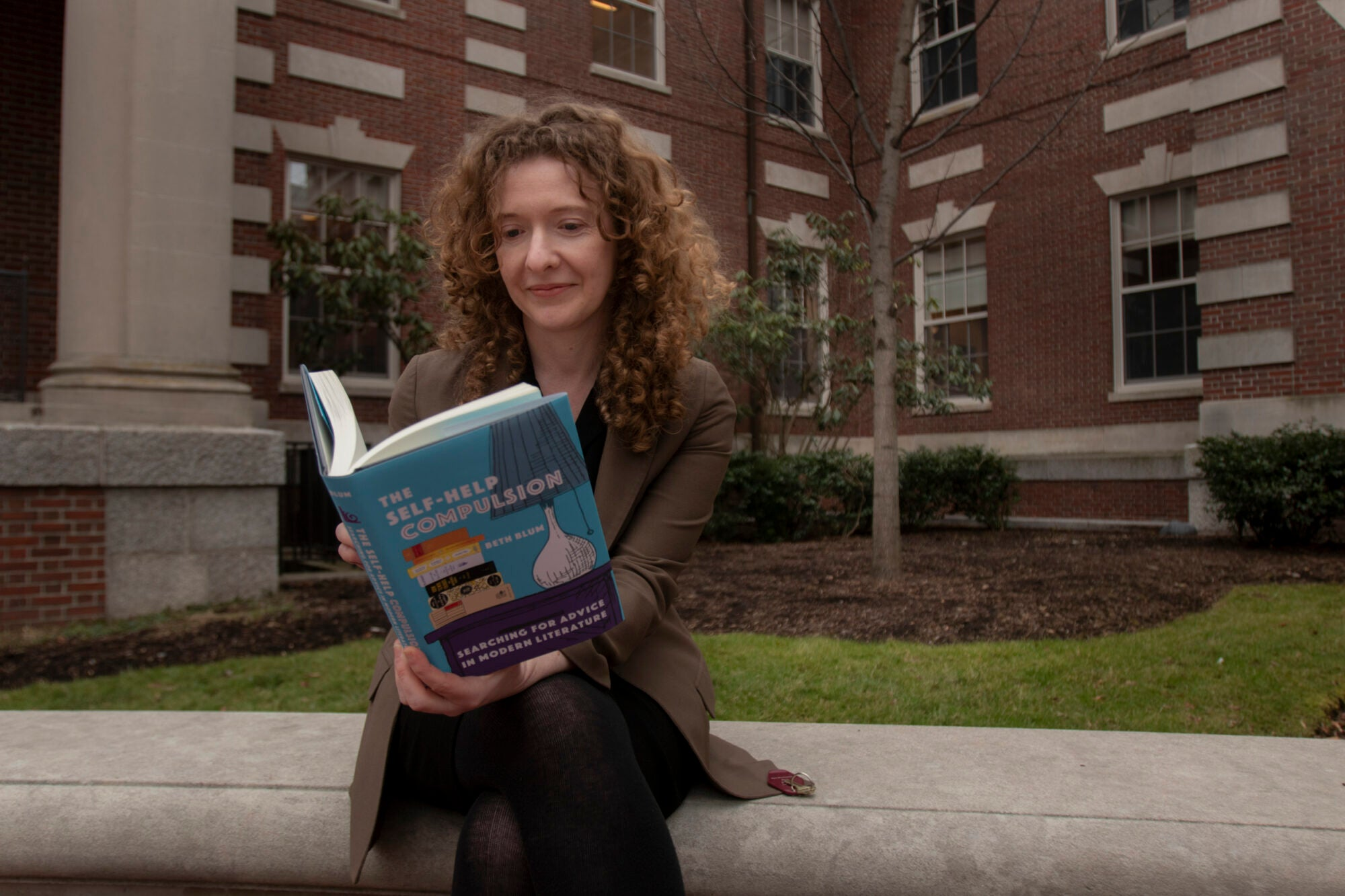 """A woman reads a book outside entitled """"The Self-Help Compulsion"""""""