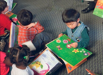 A group of small children read books on the floor