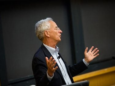 A professor talking in front of a podium