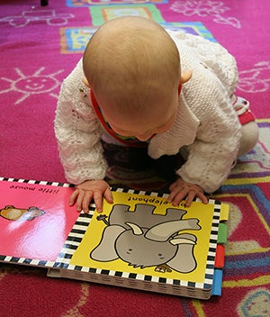 A small baby looks at a book