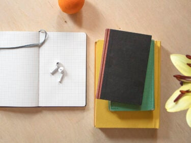 Three books piled on top of each other, a notepad, ear buds, and orange and part of a flower on a desk