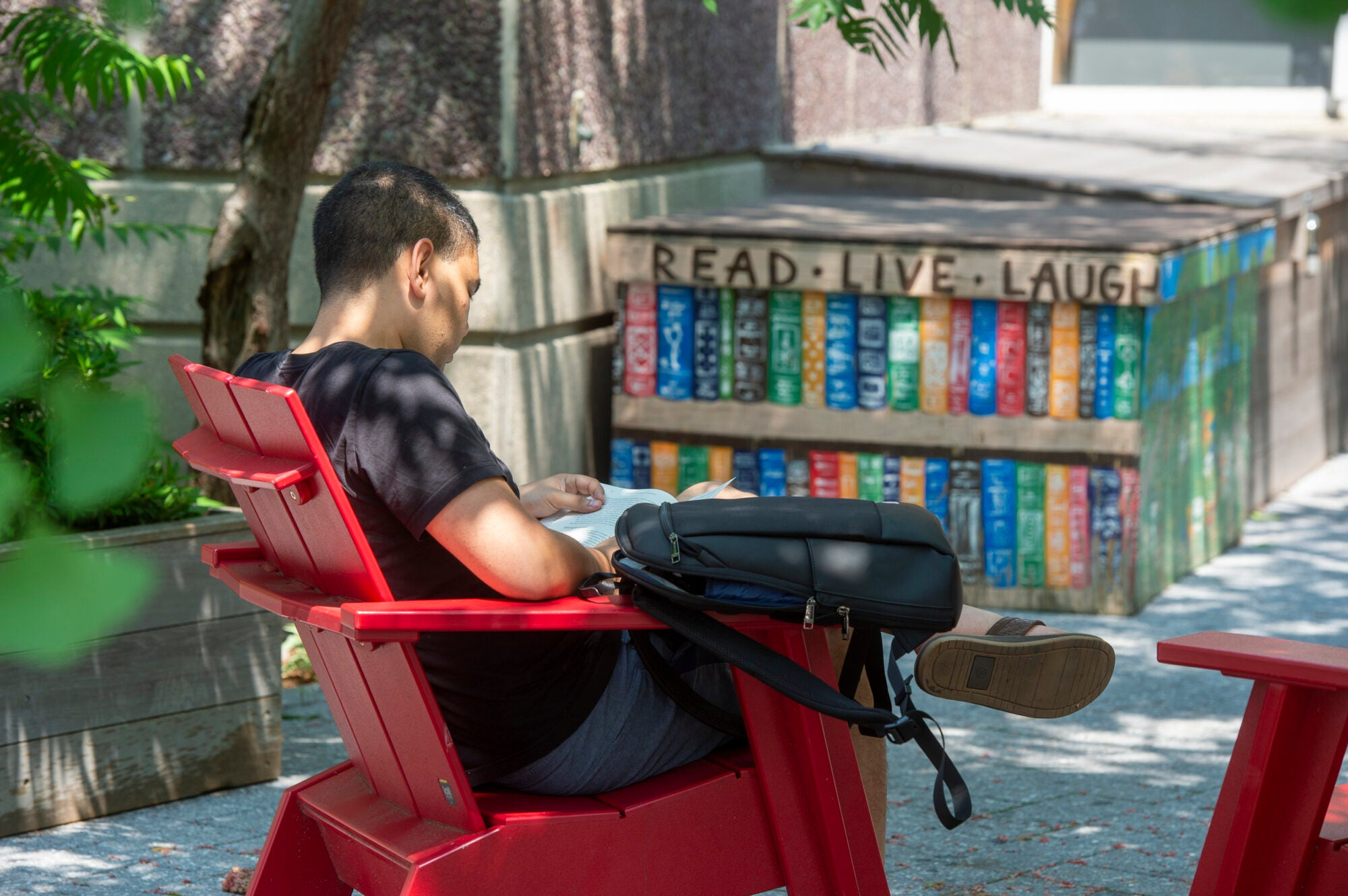 A student reads while sitting in a red Adirondack chair