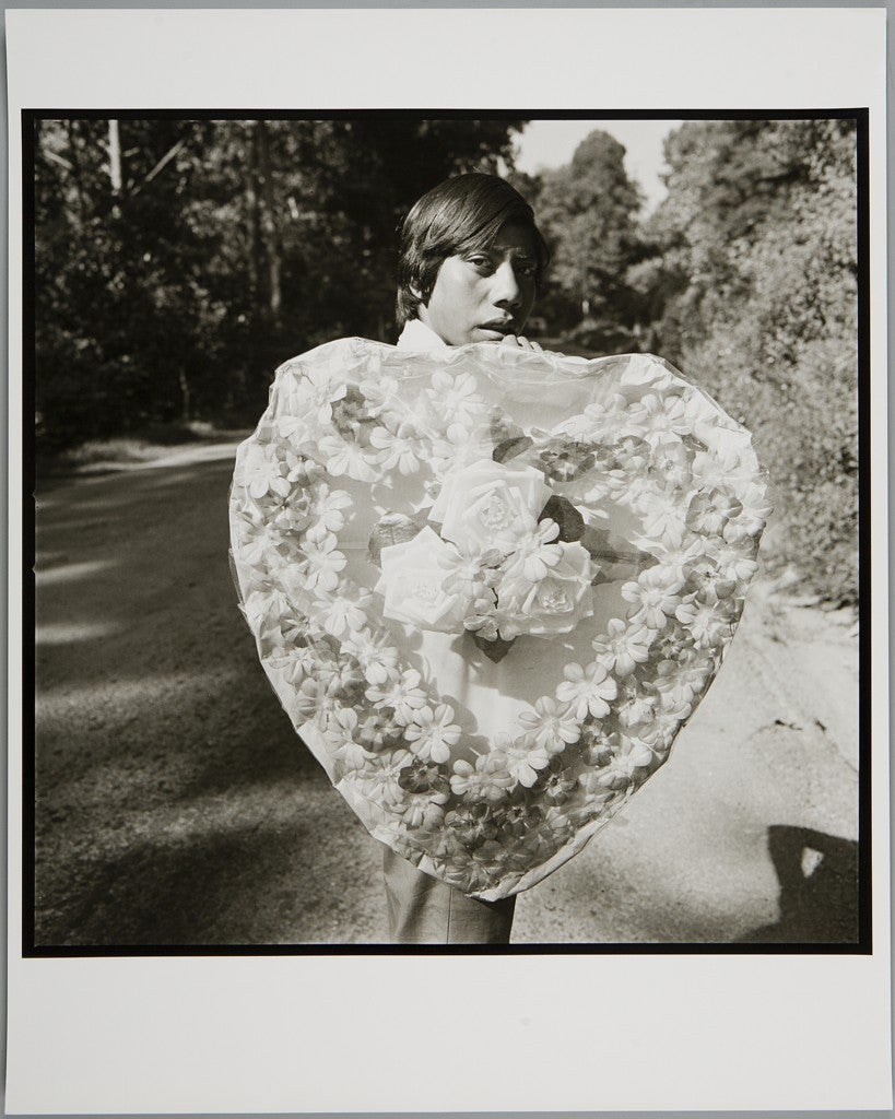 A black and white photo of a boy holding a large heart