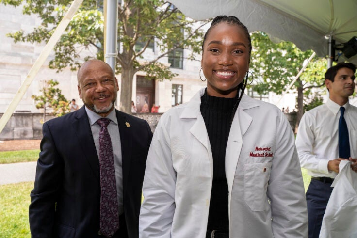 A student wearing her white coat smiles, while a faculty member looks on