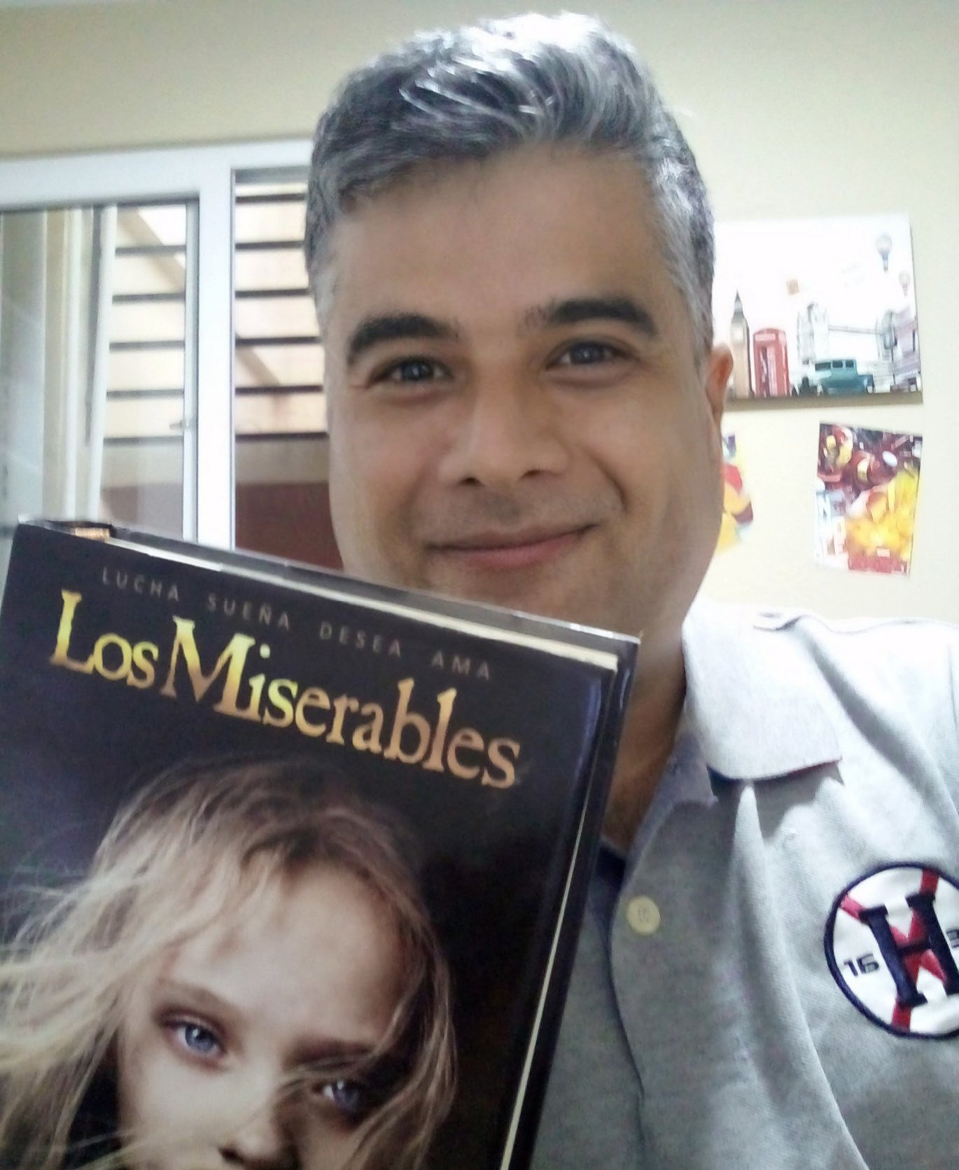 """A man stands holding a book entitled """"Los Miserables"""""""