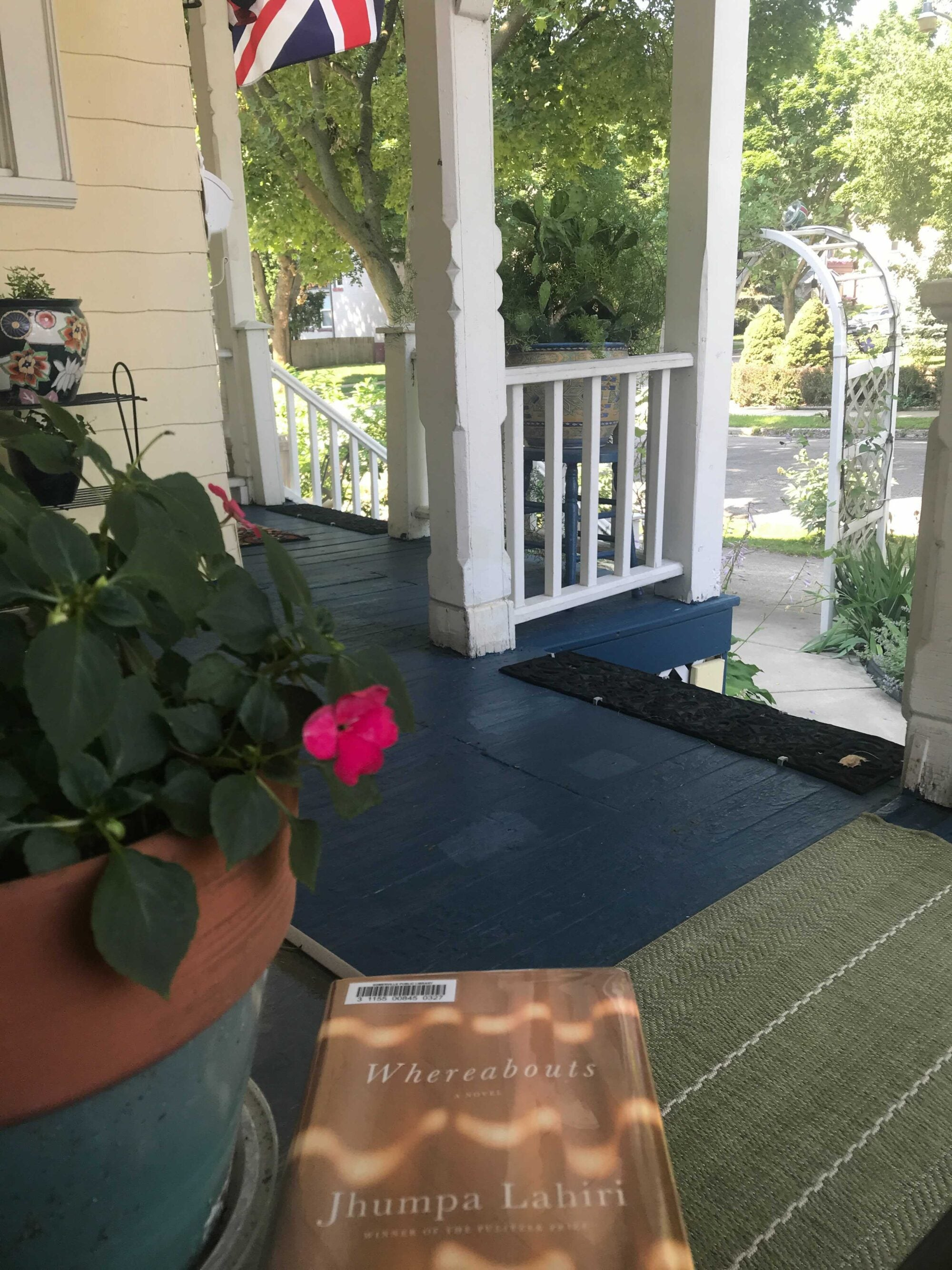 A book rests next to a potted plant on a front porch