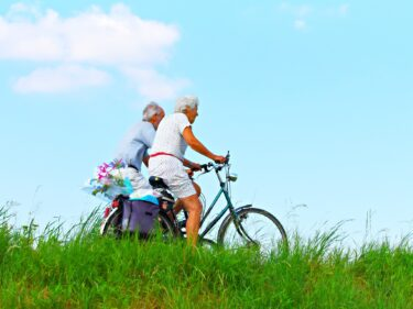 Two elderly people riding bikes