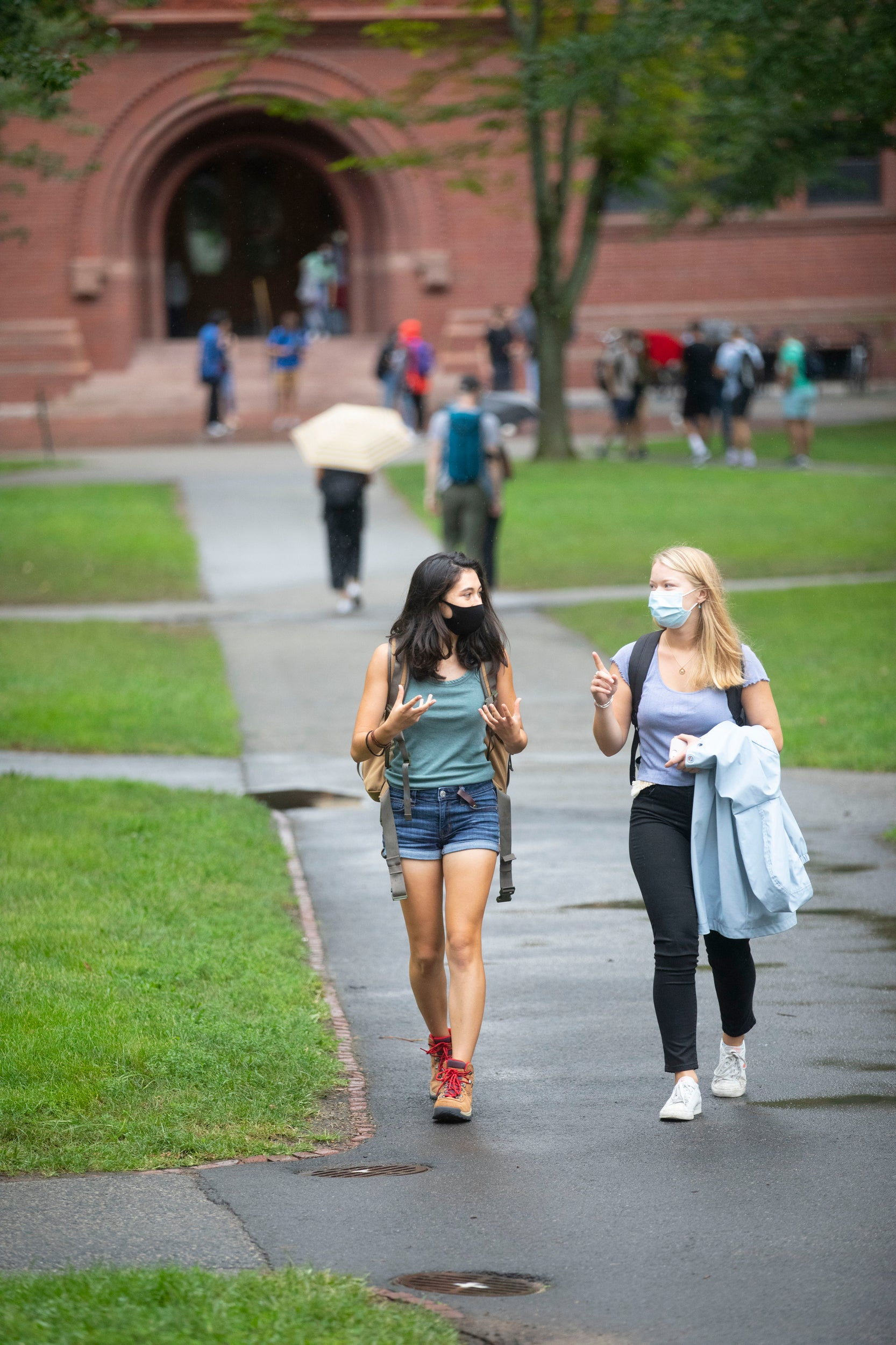 Two students wearing masks talk while walking on campus